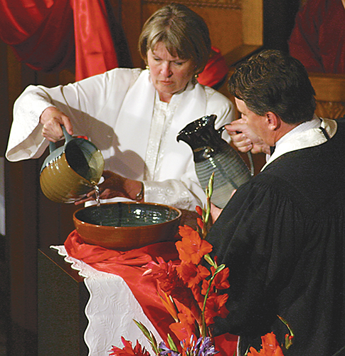 Twila Gibbens-Rickman and Lesly Broadbent take turns pouring water as 38 clergy and spouses are memorialized. (Photos by Holly McCray)