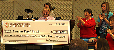 Presenting an oversized check is Pastor Norma Gravley-Quinn, while Debbie Langford and Aly Sutherlin applaud.