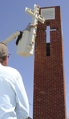 a team from Marlow reinstalls the cross in the bell tower at Velma UMC. Duncan volunteers