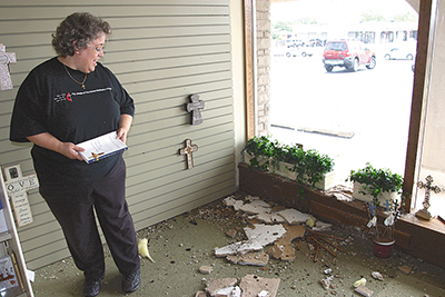 Book in hand, manager Julie Wood surveys ruined inventory, above, at the Cokesbury store in Oklahoma City on May 18. Top photo shows water leaking from the hail-damaged ceiling. The store was forced to close indefinitely. Photo by Amelia Ballew