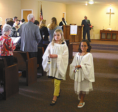 Acolytes Kelsey, left, and Savanna carry out the light of Christ on May 16 from the newly completed sanctuary of the Franklin church.