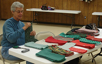 Above, Darla Carr sorts green and red Christmas stockings at Frederick UMC. A quilters group at the church made hundreds of them for elementary students. Below, gifts of sweatsuits are delivered by Chelsea Memorial UMC volunteers to a veterans care center in Claremore.