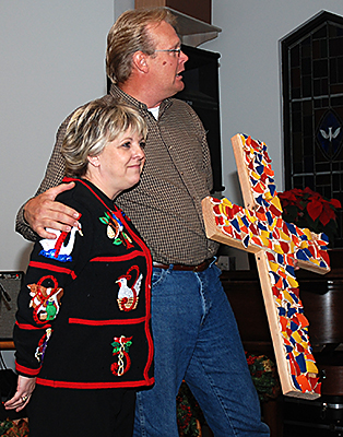 The symbolism of a cross covered in broken pottery is explained by Sharen Hale, left, pastor at Gene Autry's First United Methodist Church, and David Colaw, pastor at First Baptist.