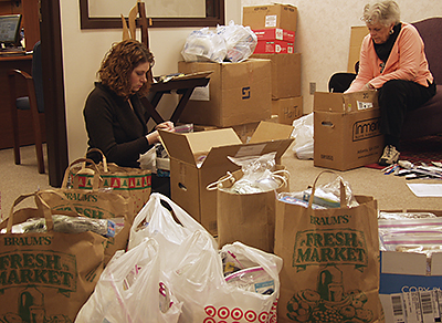 VIM's Kristin Terrell-Wilkes, left, and Mary Alice Young sort health kits for Haiti.