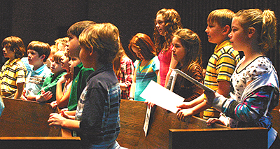 CAROLS OF THE CHILDREN—Voices fill Smith Chapel at Oklahoma City University on April 17 as youngsters from five churches rehearse during the Children's Choir Festival. Clinician and mother-to-be Amy Thomas recalled singing in the annual festival in her own childhood. Choirs came from as far away as Woodward, Tishomingo, and Ponca City, reported coordinator Andy Ste-wart. The day included worship led mostly by children and presentation by puppeteer Dave May. Pianist was Linda Owen, and organist, Elizabeth Harrison.