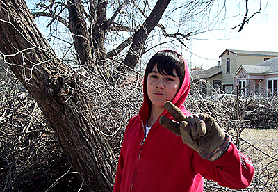 Piles of broken tree limbs surround Tony Arnold of Carnegie UMC, helping clean up after a late January ice storm in southwestern Oklahoma. He was among several volunteers during a Lawton District disaster response workday for New Light UMC, a Korean-language congregation in Lawton.