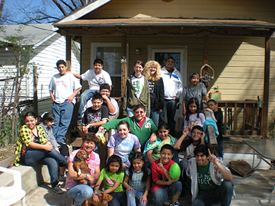 Mission team members pose with new friends at a mission site in San Antonio.