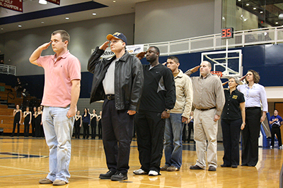 Before a spring basketball game, members of the OCU Military Affinity Group salute during a ceremony honoring military veterans. The event was in OCU's Freede Center.