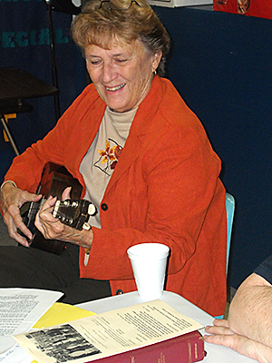 Playing a ukelele, Suzanne Carpenter leads hymn singing.