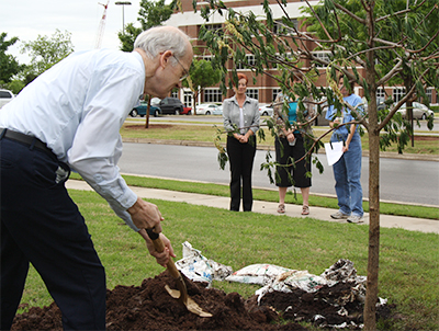 IN GOD'S GARDEN—George Elswick takes his turn as staff members plant a buckeye tree on Arbor Day, April 30, at the United Methodist Ministry Center in Oklahoma City. Elswick has been supervising the Mail Room since 1995.