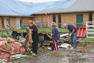In these two photos, volunteers respond on May 13 at Tulsa's Aldersgate UMC, where wind tore away a large chunk of roof that morning. Pastor Marcia Shoemaker said worship continues in the sanctuary, and structural repairs on the building will likely take months. A Montessori school housed in the church has moved temporarily. Recovery efforts also mean relocating Project Transformation, a summer literacy day camp for children. The church will continue as the host wherever the camp meets, Rev. Shoemaker affirmed.